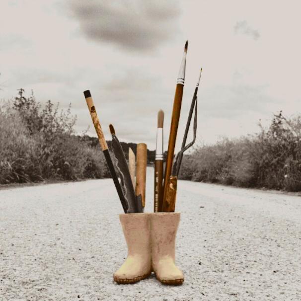 Botas en un camino, llenas de herramientas para abordar el acto creativo