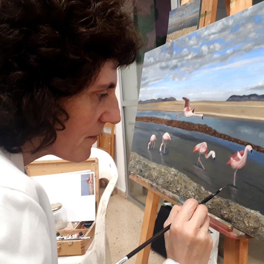 La autora pintando las ondulaciones del agua donde están los flamencos